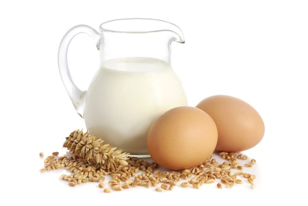 Glass jug with milk, wheat seeds and two eggs on white background