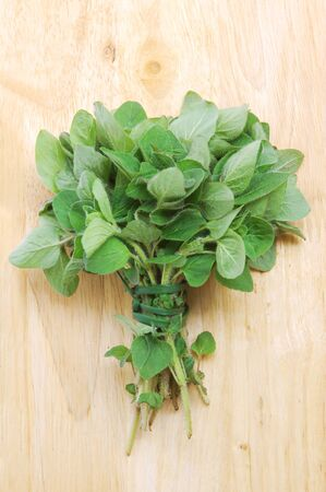 Marjoram leaves bunch on cutting board background