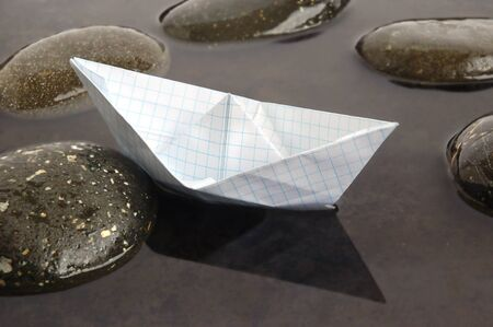 Paper boat floating in calm black water background photo