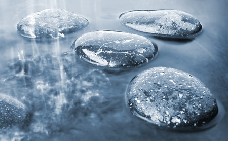 stepping: Stones in rain on black water background