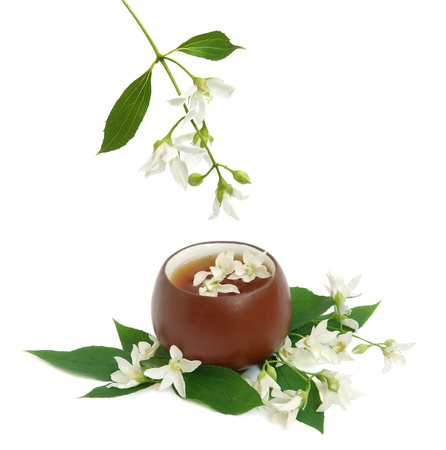 Tea leaves with fresh jasmine flowers and chinese cup on white background