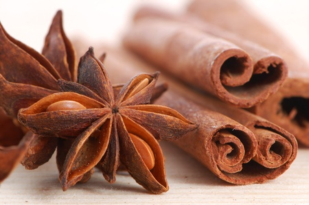 Cinnamon sticks and anise stars close-up on wood background