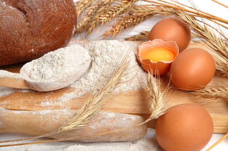 Still life of bread, eggs, cereas, flour and kitchen tools on a wooden board photo