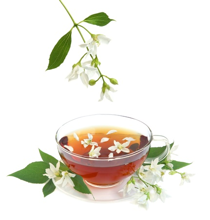 Tea leaves with fresh jasmine flowers and glass cup on white background photo