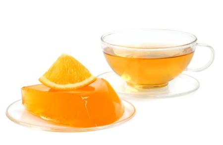 gelatina: Orange jelly con frutas y té sobre un fondo blanco Foto de archivo