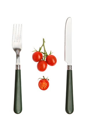 knife tomato: Close-up of a cherry tomatos with knife and fork on white background Stock Photo