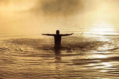 hombre orando: Silueta de un hombre con los brazos elevados en el agua