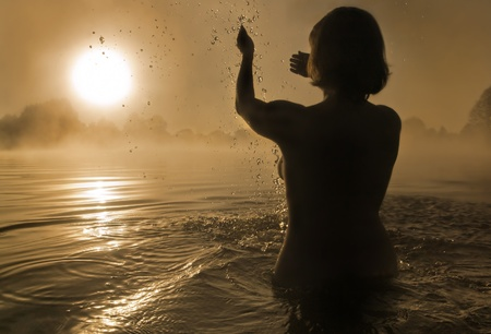 Silhouette of a young girl with raised arms in the water photo