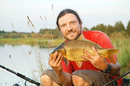 Fisherman holding a gold carp on the shoreline of a river photo