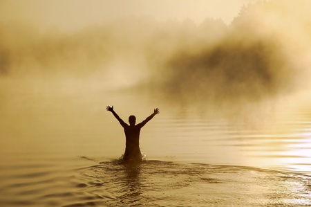 victory: Silhouette of a male with raised arms in the water