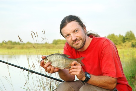 Fisherman holding a bream on the shoreline of a river photo
