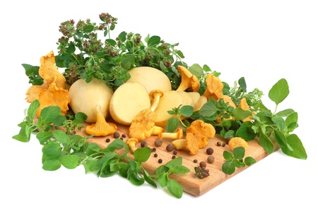 chanterelle: Yellow chanterelle mushrooms with marjoram leaves and potatos on a cutting board Stock Photo