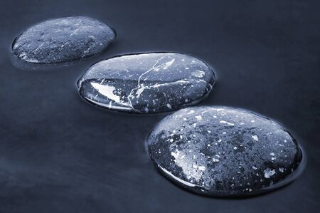 river stones: Stepping Stones on black water background