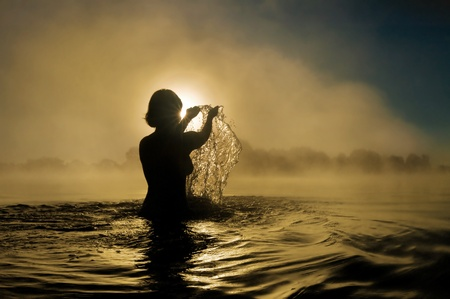 god figure: Silhouette of a young girl with raised arms in the water Stock Photo