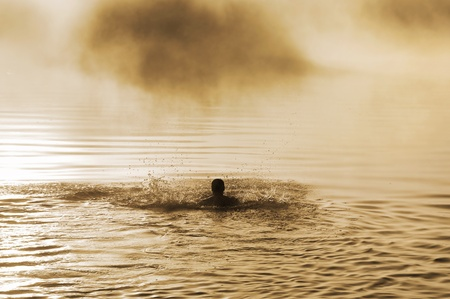 Silhouette of a male with raised arms in the water photo