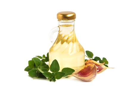 cooking oil: Cooking oil, garlic and marjoram leaves on white background