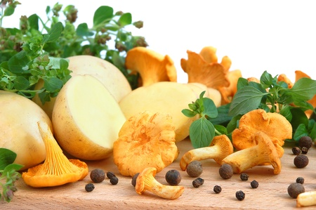 Yellow chanterelle mushrooms with marjoram leaves and potatos on a cutting board Stock Photo - 11227384
