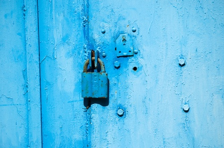 Locked steel covered door and padlock photo