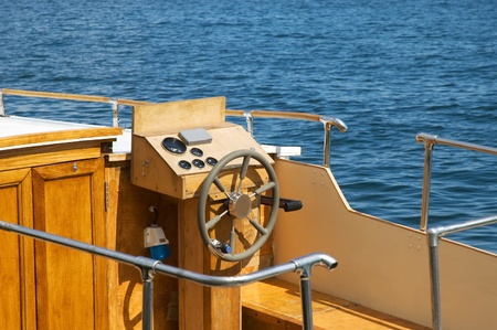 anchoring: Boat steering wheel on a wood yacht docked in a sea port.