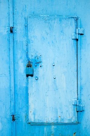 Locked steel covered door and padlock photo