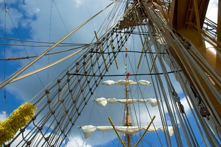 Sail and mast of old ship on a blue sky background photo
