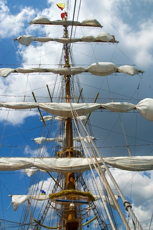 rigging: Sail and mast of old ship on a blue sky background Stock Photo