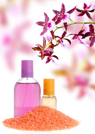 Perfume in bottle and salt over orchid background photo