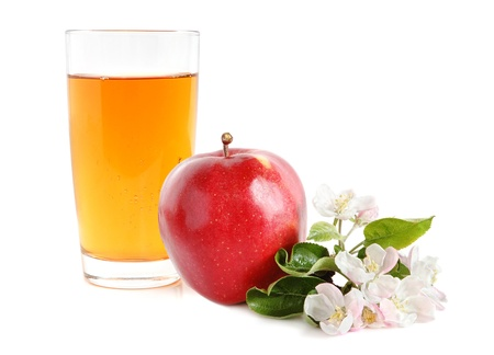 Apple juice in glass and fresh apple with green leaves and flowers on white background