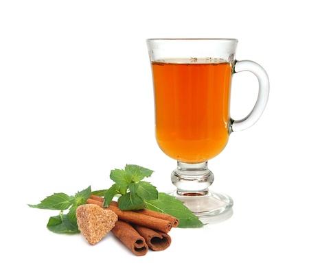 Tea, mint leaves, heart-shaped cane sugar and cinnamon sticks on white background photo