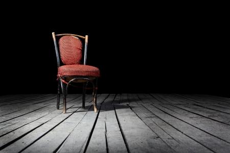 habitacion desordenada: Antiguo presidente de moda rojo sobre un suelo de madera