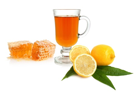 christmas tea: Hot tea in glass cup with lemon and honey on white background