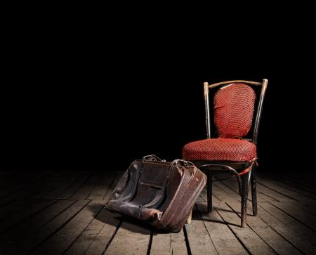 habitacion desordenada: Viejo sillón rojo y muy transitada maleta de la cosecha en el suelo de madera Foto de archivo