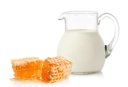 Glass jug with milk and honey on white background