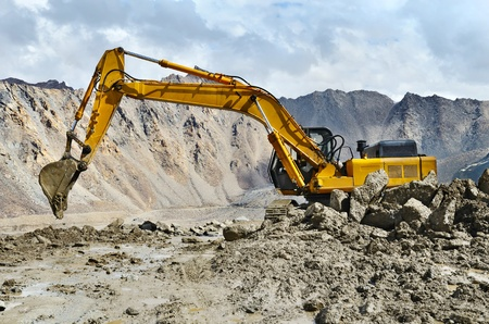 A large yellow excavator machine at work photo