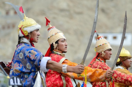 folk heritage: LEH, LADAKH, INDIA - SEPTEMBER 08, 2012: Artists in traditional tibetan costumes performing folk dance with swords and singing a song in of praise great king of Ladakh called Ling Gyalam Kaser King. Last day of Annual Festival of Ladakh Heritage in Leh, I