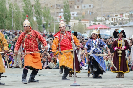 LEH, LADAKH, INDIA - SEPTEMBER 08, 2012: Artists in traditional tibetan costumes performing folk dance with swords and singing a song in of praise great king of Ladakh called Ling Gyalam Kaser King. Last day of Annual Festival of Ladakh Heritage in Leh, I