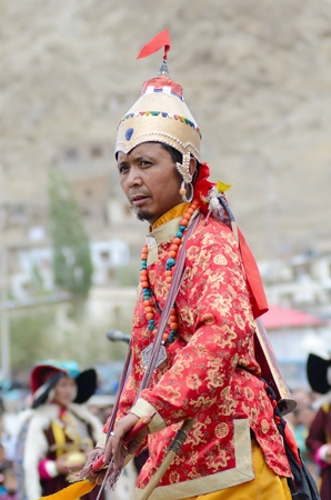 LEH, LADAKH, INDIA - SEPTEMBER 08, 2012: Artist in traditional tibetan costumes performing folk dance with swords and singing a song in of praise great king of Ladakh called Ling Gyalam Kaser King. Last day of Annual Festival of Ladakh Heritage in Leh, In