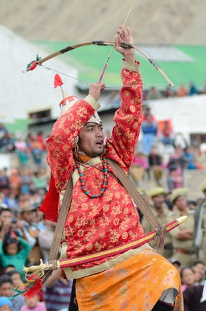 folk heritage: LEH, LADAKH, INDIA - SEPTEMBER 08, 2012: Artist in traditional tibetan costumes performing folk dance in praise of great king of Ladakh. Annual Festival of Ladakh Heritage in Leh, India. September 08, 2012.