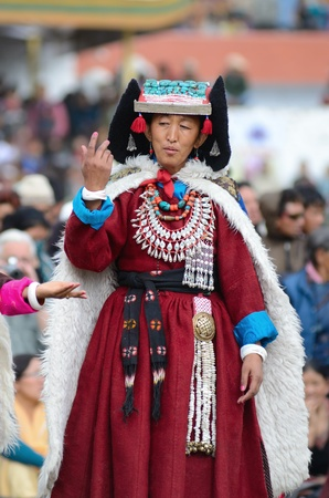 LEH, LADAKH, INDIA - SEPTEMBER 08, 2012: Woman in traditional tibetan costumes performing folk dance. Last day of Annual Festival of Ladakh Heritage in Leh, India. September 08, 2012.