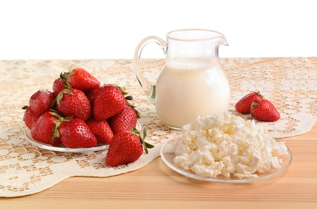 Ripe strawberries, milk and cottage cheese on a crocheted table-cloth photo