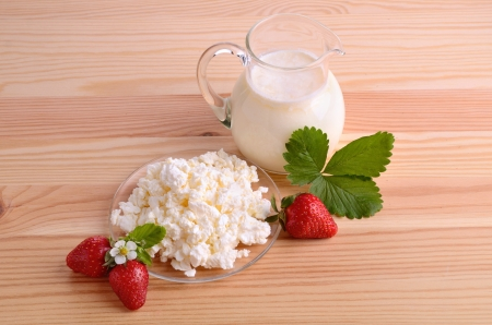 Ripe strawberries, milk and cottage cheese on wood table photo