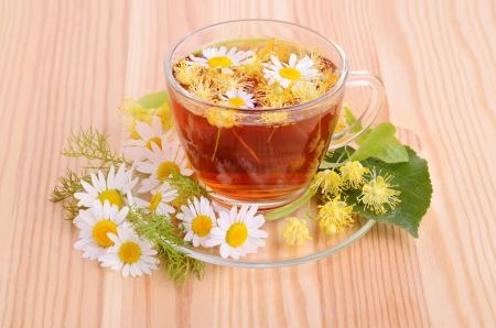 Herbal tea in glass cup with linden and camomile flowers on a wood table background photo
