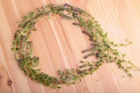 Frame from thyme flowers on a wood table background photo