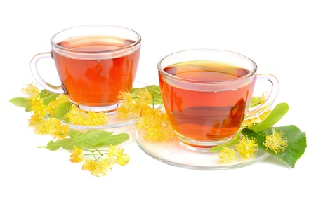 Two cups with herbal tea and linden flowers on a white background photo