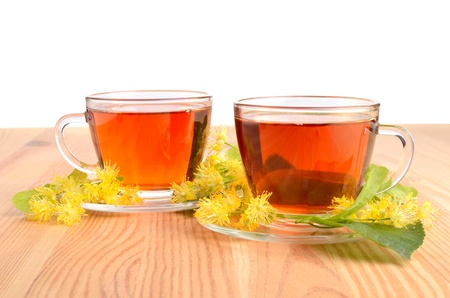 Herbal tea with linden flowers on a wood table background photo