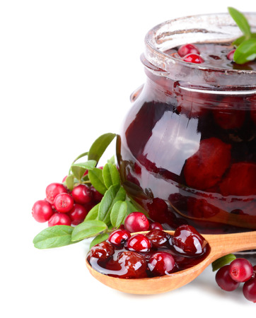 marmalade: Close up of cowberry jelly in wooden spoon and in jar with fresh berrys on a white background