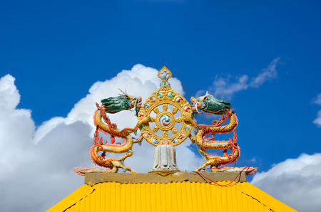 dharma: Two dragons statue with Wheel of Dharma on roof of monastery Gates Stock Photo