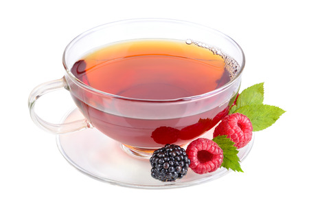 Black tea in cup with raspberries and blackberries on white background photo