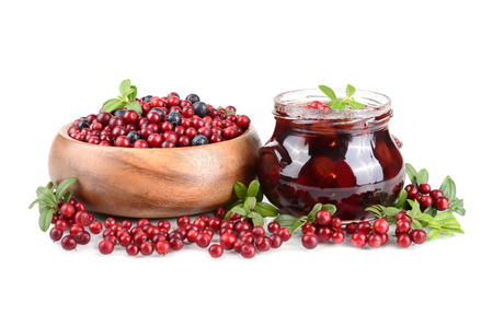 Cowberry jelly and fresh berrys in a round wooden bowl on white background photo