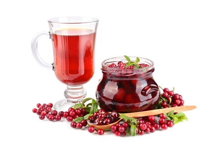Cowberry jam, small spoon and black tea on white background photo